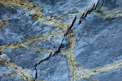 Detail of a rock with variants of blue and yellow. Rock full of traces and smooth cuts resulting from the erosive effect of sea. Close up rocks erosion formation. Natural texture and colorful.