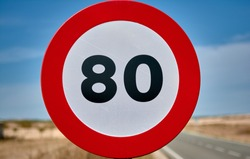 detail of a round traffic sign with red border and black limit number 80 km/h mph