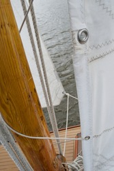 Detail of a sail attached to the wooden mast of a sailing boat while afloat and under sail, sailing over grey water. Eyelets in the white sail fabric, thin rope wrapped round a brown mast and a wooden