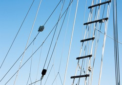 Detail of a sailboat rigging and rope ladder against the blue sky