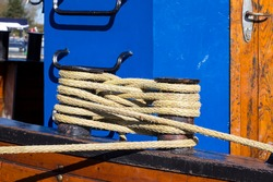 Detail of a sailing ship, attachment for the ropes. Sighted on the Baltic Sea coast. In the background the cabin glows with a blue colour.
