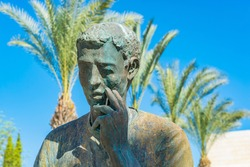 Detail of a sculpture of a man against a background of palm trees.