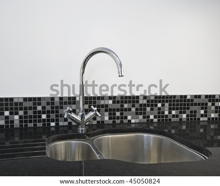 detail of a stainless steel kitchen sink on a black granite worktop