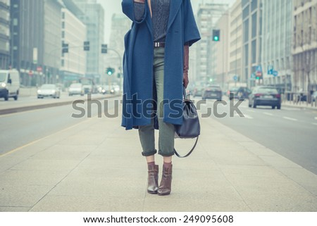 Detail of a stylish young woman posing in the city streets