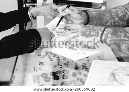 detail of a tattoo design of a tattoo artist is showing to a young female customer the tattoo design before the tattoo session at the tattoo shop focus on the tip of the pen