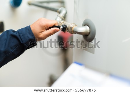Detail of a technician opening a valve
