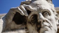 detail of a thinker statue in front of the Palazzo della Cassazione in Rome