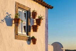 Detail of a traditional house painted in white and blue, with a window with pottery vases, near Mafra, Portugal.
