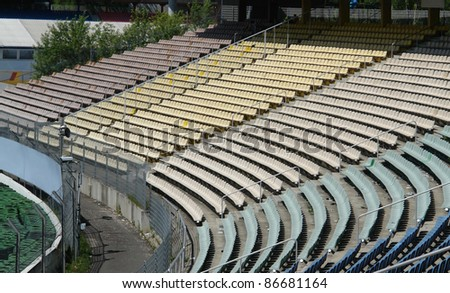 "detail of a tribune on a racetrack named ""Hockenheimring"" in Southern Germany with lots of colored chairs at summer time"