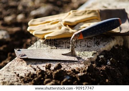 Detail of a trowel and protective gloves at the end of a workday
