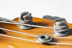 Detail of a tuning post on the wooden headstock of an electric bass guitar. Musical instruments and mechanics for string tuning.