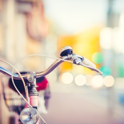 Detail of a Vintage Bike HandleBar with a Colorful Background Bokeh Made of Busy Traffic