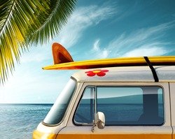 Detail of a vintage van in the beach with a surfboard on the roof