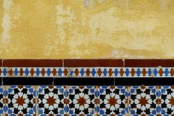 Detail of a wall in Seville's Casa Pilatos,  Southern Spain. Half beautiful ceramic tiles (azulejos) with geometric patterns and half yellow concrete wall.
