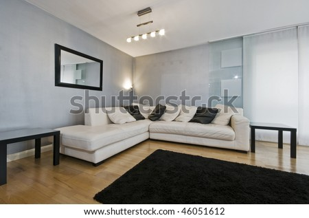 Photo detail of a white leather corner sofa in a living room with blue