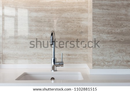 Detail of a white rectangular designer kitchen sink with chrome water tap against a tiled wall