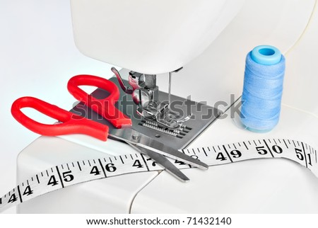 Detail of a white sewing machine with a measuring tape,scissors and blue thread