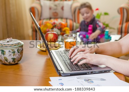 Detail of a woman hands writing in notebook and boy playing on the background. Home office concept. #188339843