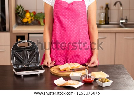 Detail of a woman in the kitchen wearing apron and making hot sandwiches for brakfast in a sandwich maker. Focus on the sandwich maker and the apron