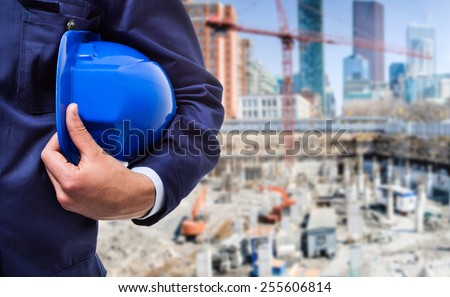 Detail of a worker in front of a construction site