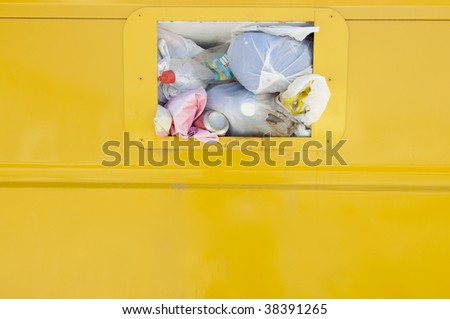 Detail of a yellow recycling container overflowing