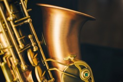 Detail of alto saxaphone, over black background.