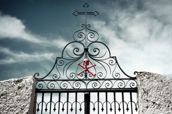 Detail of an ancient cemetery gate with a skull and crossed bones painted red