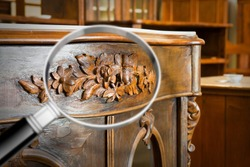 Detail of an antique wooden italian furniture just restored with a magnifying glass on foreground looking for woodworm threat detection - concept image