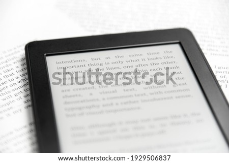Detail of an electronic reader with the screen on and a text on it, on sheets of paper with text printed on them. Concepts: reading and digital technology. Stock photo ©