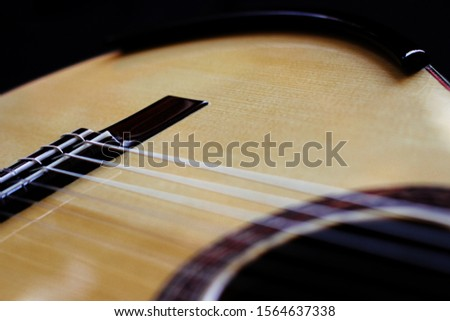Detail of an elegant classical guitar with spruce top with ebony bridge arm rest
