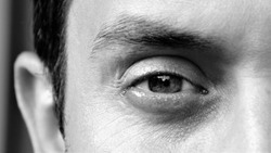 Detail of an eye of a handsome man looking at camera. Details of a male face, closeup. Black and white photo