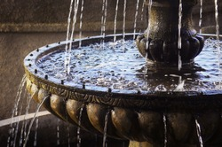 Detail of an old classic style stone fountain with flowing water