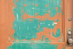 Detail of an old door on a factory or warehouse showing two layers of paint that are peeling away; useful for textured background