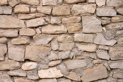 detail of an old irregular stone wall with mortar