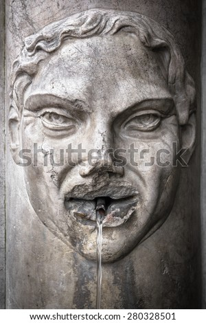Detail of an old Italian fountain whose jet of water flows from the mouth of a face carved in marble.