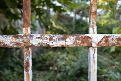 Detail of an old rusty metal fence with and old overgrown house in blurred background. Horizontal image with geometric concept and copy space