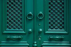 detail of an old-style wooden door in dark green color, classic entrance green door