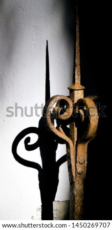 Detail of and old ornamental and rusty iron fence with its shadow #1450269707