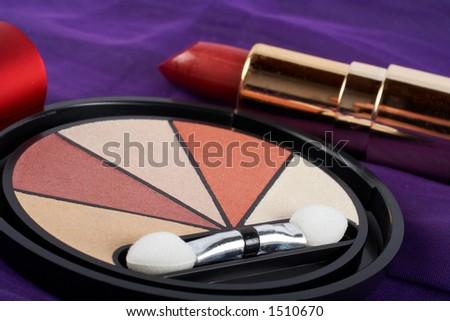 Detail of assortment of makeups.  Macro shot on malva background. Very shallow dof