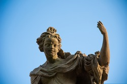 Detail of baroque statue with clear blue sky. Virtues and vices. Diligence. Sunset light relecting on the limestone masterpieces.