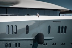 Detail of beautiful Superyacht, deckhand lifting the huge fender of the starboard side of the megayacht, spotless grey and white superstructure