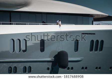 Detail of beautiful Superyacht, deckhand lifting the huge fender of the starboard side of the megayacht, spotless grey and white superstructure Stockfoto ©