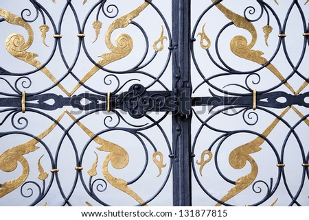 Detail of black and golden ornamental iron wrought gate.