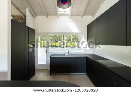 Detail of black modern kitchen with window view. Nobody inside