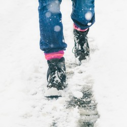 Detail of Boots Walking in Fresh White Snow