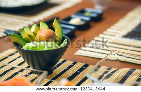 Detail of bowl of avocado cut along with other ingredients ready to prepare sushi