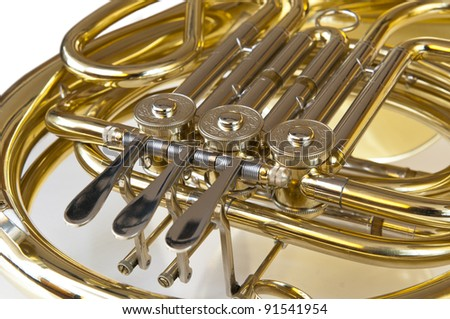 detail of brass and silver horn or bugle with valves lying on a white background