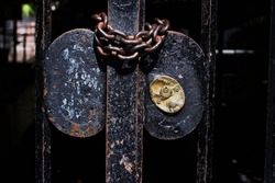 Detail of brass lock and chain of a partially rusted iron gate, dark background.