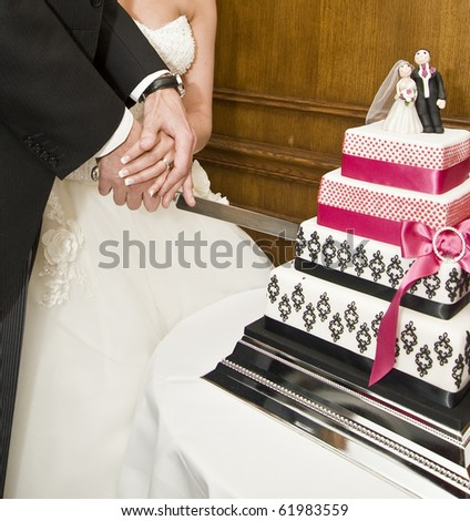 Detail of bride and groom cutting wedding cake after getting married