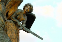 Detail of bronze statue, angel with sword in hand, background of clear blue sky. Altar of the Fatherland in Rome.